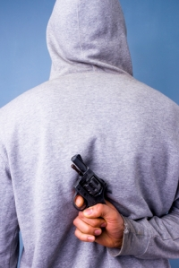 Hooded man hiding gun behind his back